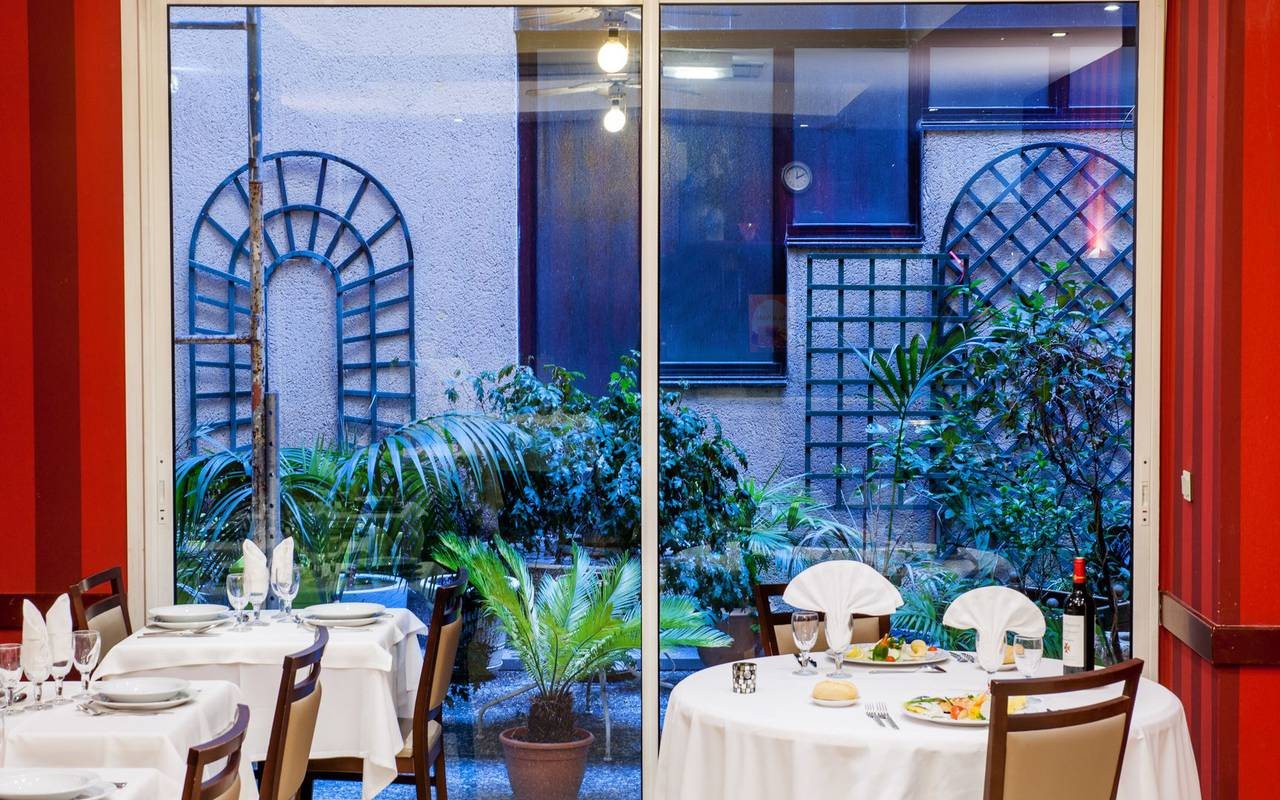 Meal in the restaurant with a view on a large bay window giving onto a small terrace, hotels in lourdes near grotto, Hotel Saint-Sauveur.