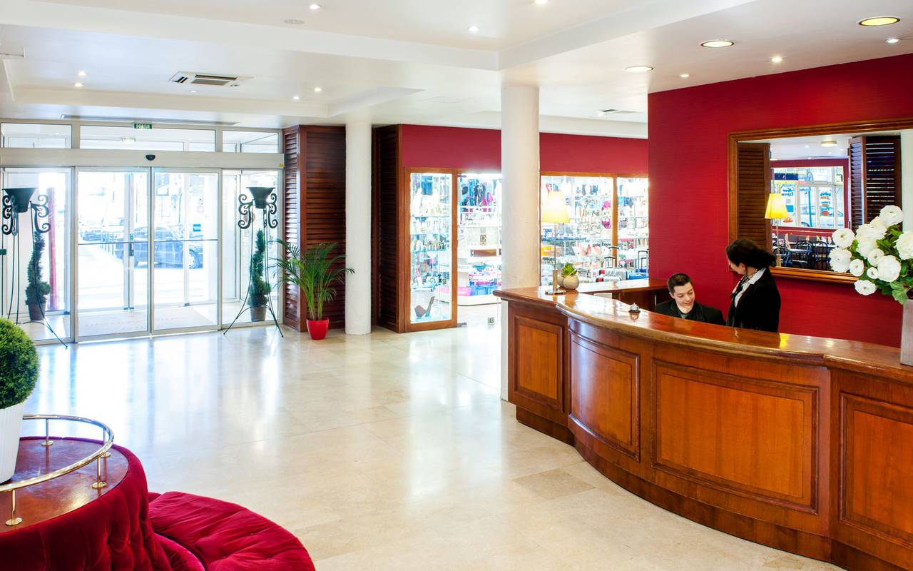 Red colored reception with warm and smiling staff, hotels in lourdes near grotto, Hotel Saint-Sauveur.