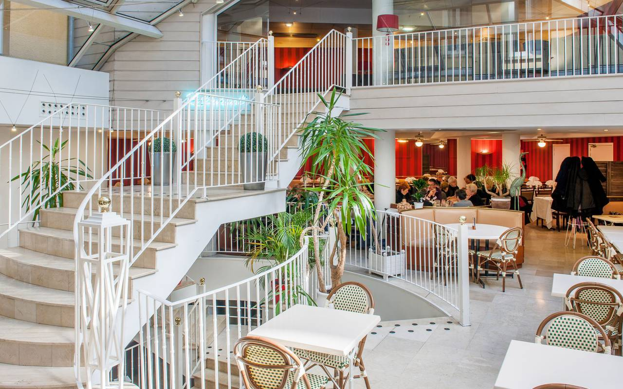 Large hall with reception and tables next to the large staircase to the rooms, restaurants in lourdes france, Hotel Saint-Sauveur.