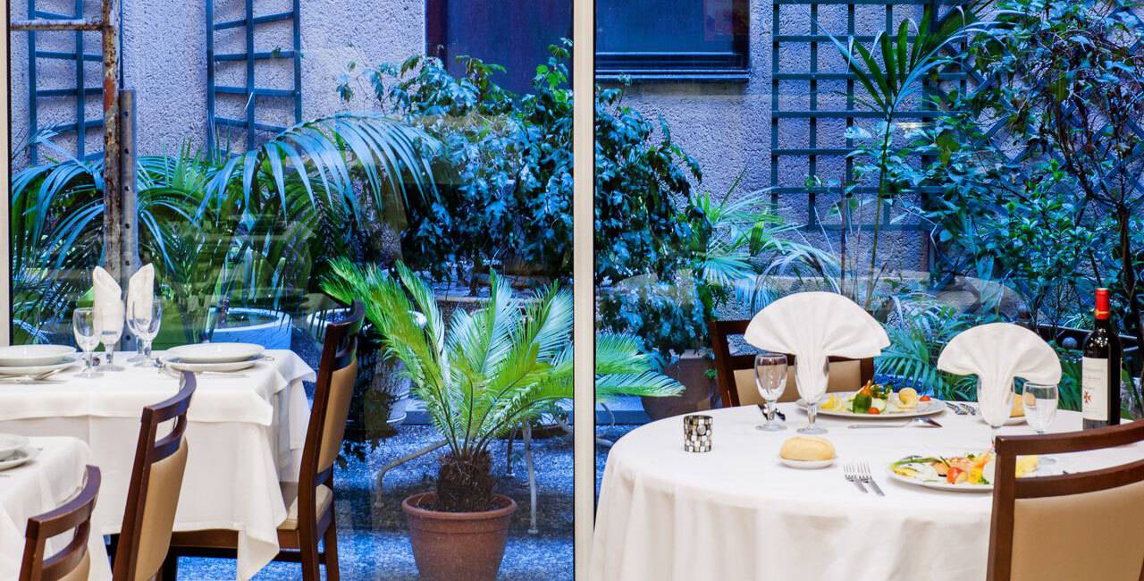 Restaurant table overlooking our outdoor living space with trees and flowers, restaurants in lourdes france, Hotel Saint-Sauveur.