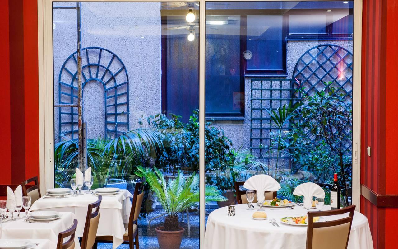 Repas au restaurant avec vue sur une grande baie vitrée donnant sur une petite terrasse, hotel lourdes proche sanctuaire, Hôtel Saint-Sauveur.