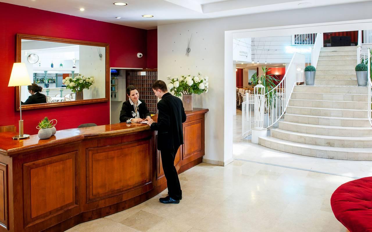 Hall d'entrée avec réception à gauche et de grands escaliers vers les chambres, hotel restaurant pyrenees, Hôtel Saint-Sauveur.