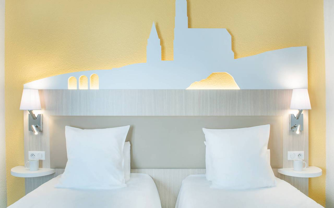 Lit double confortable avec table de nuit et lampe, hotel lourdes centre ville, Hôtel Saint-Sauveur.