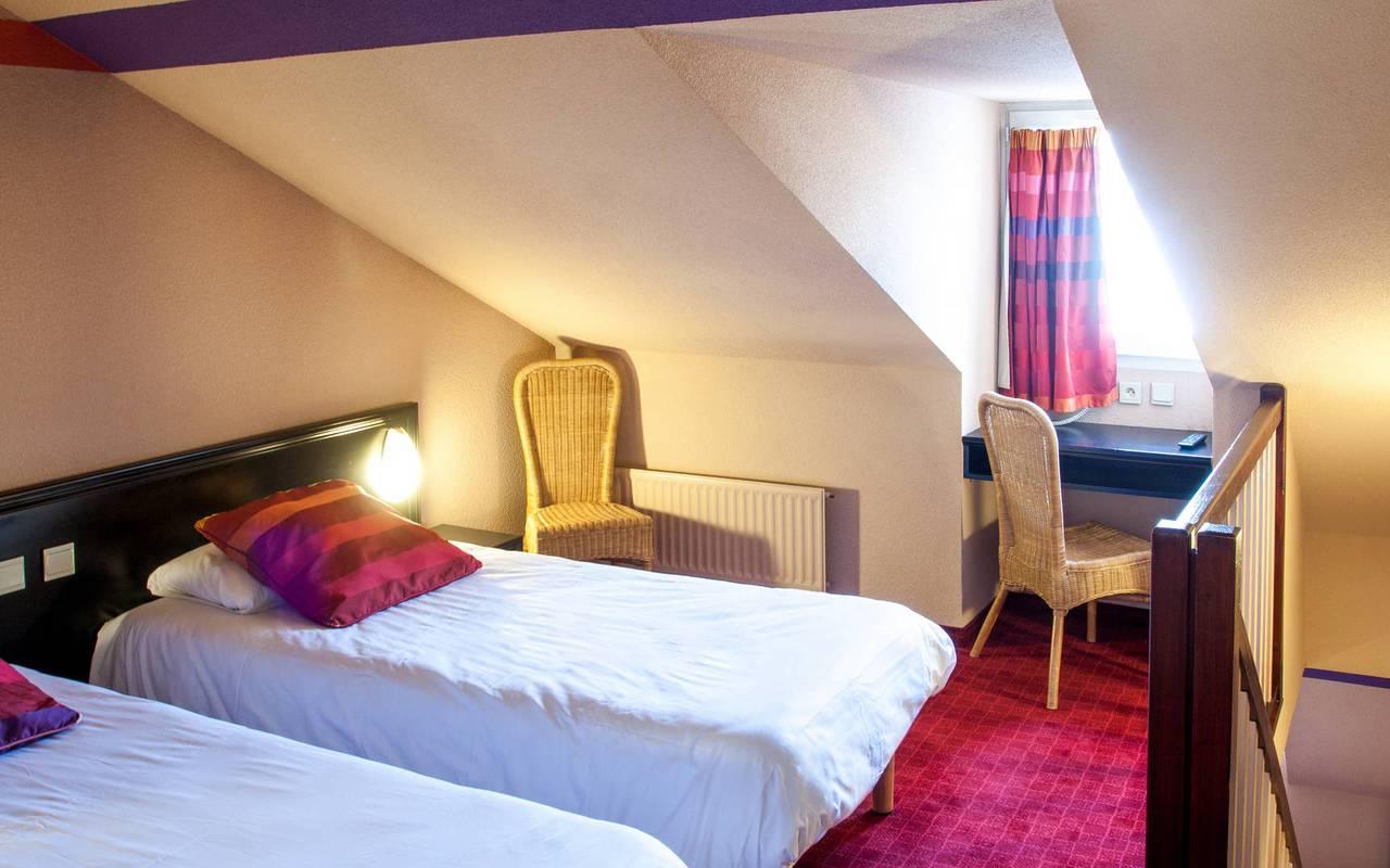 Deux lits simples en haut des escaliers dans la chambre duplex, hébergement hautes pyrénées, Hôtel Saint-Sauveur.